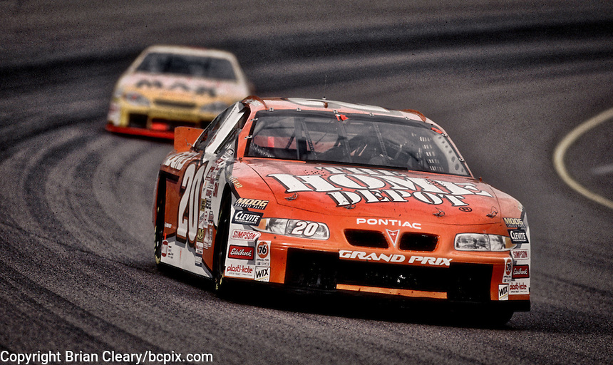 Tony Stewart leads Bobby Hamilton of turn two during the Checker Auto Parts/Duralube 500K at Phoenix International Raceway in November 2000. (Photo by Brian Cleary/www.bcpix.com)