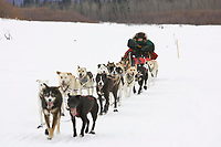 Peter Bartlett kneels on his runners as his teams runs down the Kuskokwim river shortly before McGrath on Wednesday during Iditarod 2008