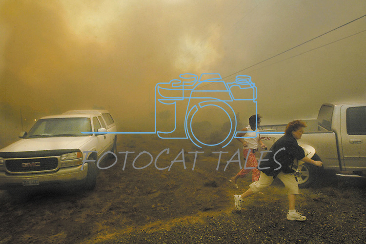 Pleasant Valley residents, near Reno, Nev., scramble to escape as the Andrew fire overruns the neighborhood Aug. 24, 2004. .Photo by Cathleen Allison/Copyright Nevada Appeal
