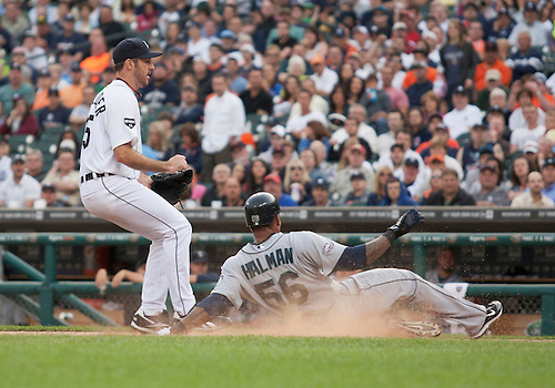 June 09, 2011:  Seattle Mariners left fielder Greg Halman (#56) slides into home to score run on wild pitch as Detroit Tigers starting pitcher Justin Verlander (#35) covers the plate in game action during MLB game between the Seattle Mariners and the Detroit Tigers at Comerica Park in Detroit, Michigan.  The Tigers defeated the Mariners 4-1.