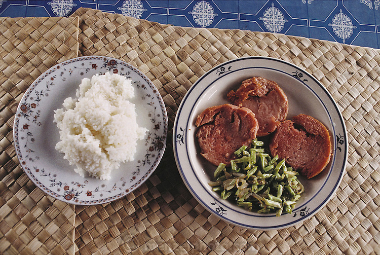 White rice and fried SPAM with green beans are part of the White Sunday feast at the Lagavale home in Poutasi Village, Western Somoa. The family sits on the floor on hand-woven mats. The Lagavale family lives in a 720-square-foot tin-roofed open-air house with a detached cookhouse in Poutasi Village, Western Samoa. The Lagavales have pigs, chickens, a few calves, fruit trees and a vegetable garden. Material World Project.