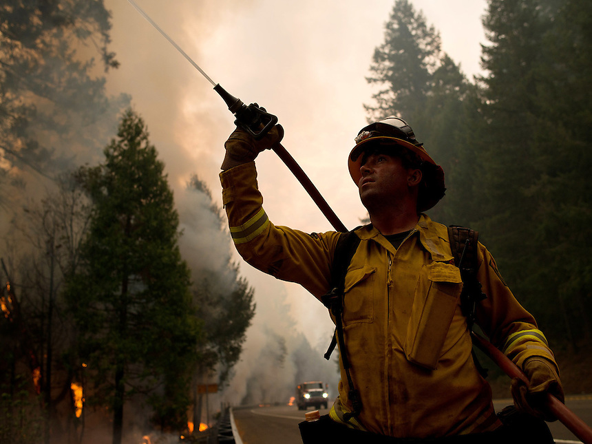 A firefighter sprays flames on low tree branches during controlled firing operations to create a wide fire break along US Route 50 near the town of Pollock Pines, California, USA, on 18 September 2014. Fire crews around California fight 12 major fires across the state, including the King Fire, located 56 miles (90 kilometers) east of Sacramento, California, which more than doubled in size overnight to 70,994 acres (28,730 hectares) and 5% contained.