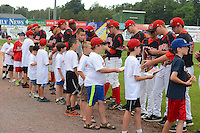 Batavia Muckdogs players sign autographs for campers before a game against the Hudson Valley Renegades on August 8, 2013 at Dwyer Stadium in Batavia, New York.  The game was cancelled in the third inning with Batavia leading 1-0 due to rain storms.  (Mike Janes/Four Seam Images)
