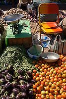 Tomatoes and aubergines in front of an orange chair at the Friday market in Mapusa.