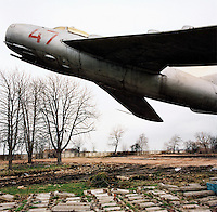 A Mikoyan (MiG) airoplane suspended above the ground as part of an installation on a deserted Soviet airforce base.. CHECK with MRM/FNA