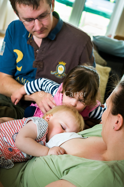 A mother breastfeeds her baby while sitting on a sofa.  Her husband holds their older daughter while she kisses the head of her baby sister.<br /> <br /> Taken: 01/05/2011<br /> Hampshire, England, UK