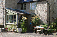 In the shelter of the porch a large collection of plants in containers flourish against the grey stone walls of the farmhouse