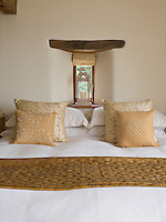 Instead of a headboard the bed in the master bedroom is placed against a wall with an original arrow-slit window