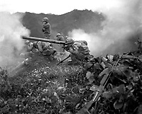 Pfc. Roman Prauty, a gunner with 31st RCT (crouching foreground), with the assistance of his gun crew, fires a 75mm recoilless rifle, near Oetlook-tong, Korea, in support of infantry units directly across the valley.  June 9, 1951.  Peterson. (Army)<br /> NARA FILE #:  111-SC-369801<br /> WAR & CONFLICT BOOK #:  1435
