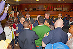 MAY 9, 2011 - MINEOLA, NY: Nassau County Police Officers called to scene of protest during public hearing of Nassau County Legislative proposed Redistricting. Seen from back and wearing green sweater, Ramel Smith of Hempstead holding hand over (out of view) his young son in front of him. The police officers were already in the building. Recess was called when Regis Lawrence Thompson at podium was told by Nassau County Presiding Officer Peter Schmitt that the man called to speak could not give Thompson his turn, though people had given their turn to others earlier, and Thompson refused to give up microphone. No arrests. At Nassau County Executive and Legislative Building, 1550 Franklin Avenue, Mineola, New York, USA on May 9, 2011