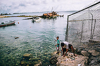Children fishing near the wreck of a boat, off the shore of Ebeye.