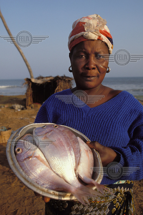 Woman sells fish beside the beach.