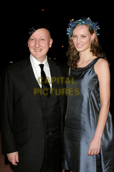 STEPHEN JONES & GUEST.Hats: An Anthology By Stephen Jones - Private View at the Victoria & Albert Museum, London, England..February 23rd, 2009 .V&A V & A half length suit jacket blue dress black hat  .CAP/AH.©Adam Houghton/Capital Pictures.