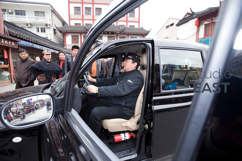 A man tests sitting in the driver's seat of a 'black cab', famous in London, parked in Shanghai's old town neighborhood, in Shanghai, China, on March 23, 2009.  London Taxi International, the producer of London Taxi's famed black cabs, turned to China to drive overseas expansion. More than 8,000 London Taxis will be produced from the Chinese factory, more than double the annual output of the firm's historical factory plant in Conventry, England. Most of these cars will go to places like Singapore, Dubai, Moscow, that covet the image associated with the London Taxis' tradition of good service and durability. London Taxi International will continue to build 90 percent of the Taxi cabs used in Britain at Coventry. Photo by Lucas Schifres/Pictobank