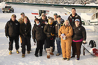 "February 16, 2013  Logistics volunteers pose for a photo at the Willow airport during the first day of the ""Food Fly"" activities.  This is where musher's food bags, straw, HEET and people food is flown by the Iditarod Air Force to the 4 checkpoints on the east side the Alaska Range. ..Photo Copyright Jeff Schultz  -- Do not reproduce without written permission"