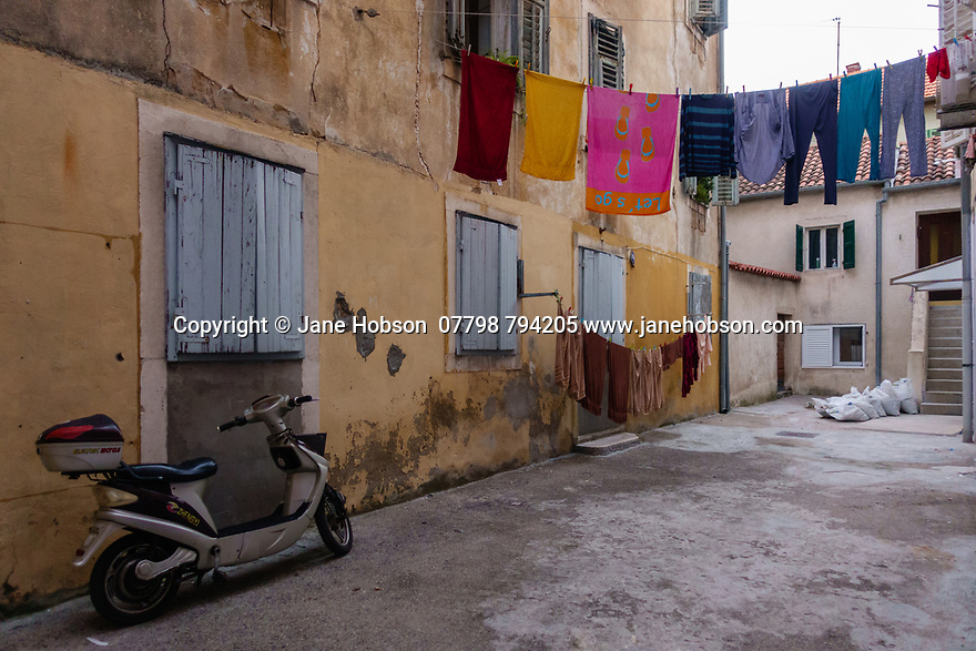 Zadar, Croatia. 17.10.2018. Residential area ,with drying washing and a motorbike, in the Old Town, Zadar, Croatia. Photograph © Jane Hobson.