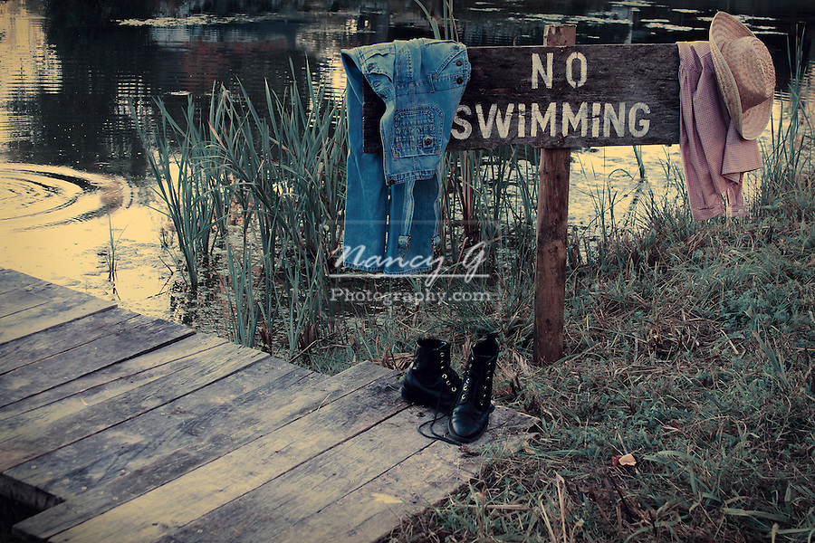 NO Swimming sign by a pond with vintage clothes hanging from sign