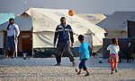 A man plays football with his children--one in his arms--in the Zaatari Refugee Camp, located near Mafraq, Jordan, while another man, wounded in fighting in Syria, looks on. Opened in July, 2012, the camp holds upwards of 50,000 refugees from the civil war inside Syria. International Orthodox Christian Charities and other members of the ACT Alliance are active in the camp providing essential items and services.