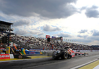 Feb 7, 2014; Pomona, CA, USA; NHRA top fuel dragster driver Leah Pritchett (near Lane) races alongside Sidnei Frigo during qualifying for the Winternationals at Auto Club Raceway at Pomona. Mandatory Credit: Mark J. Rebilas-