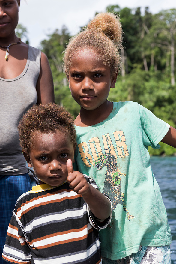 Russell Islands, Solomon Islands; local children standing on the back deck of a liveaboard dive boat, while visiting with their mother to deliver fresh fruits and vegetables in their canoe