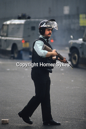 RUC officer armed patrolling street of Belfast during riots immediately afterwards Bobby Sands funeral. 1981