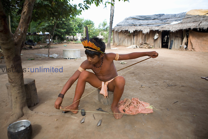 Xingu Indian boy preparing his bow and arrow for hunting, amazon Basin, Brazil.