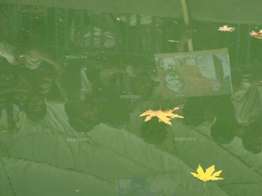 AFGHANISTAN - PROVINCE DE SAMANGAN - AYBAK - 5/08/2009 : Rassemblement de population, en majorite Ouzbek, venue ecouter et soutenir le Dr. Abdullah Abdullah, candidat aux elections presidentielles afghanes de 2009. .Feuilles d'erable jaunies par l'automne, flottant dans le bassin d'un parc ou le Dr. Abdullah Abdullah tient un discours. La foule venue l'écouter et brandir des pancartes de soutien en sa faveur se reflete dans l'eau. ..AFGHANISTAN - SAMANGAN PROVINCE - AYBAK - 5/08/2009 : At a rally where mostly ethnic Uzbeks have gathered in support of Dr. Abdullah Abdullah, candidate in the 2009 Afghan presidential elections..In the park where Dr. Abdullah Abdullah speaks, yellow autumn leaves float in a pond. The reflection of a crowd of supporters brandishing can be seen in the water.