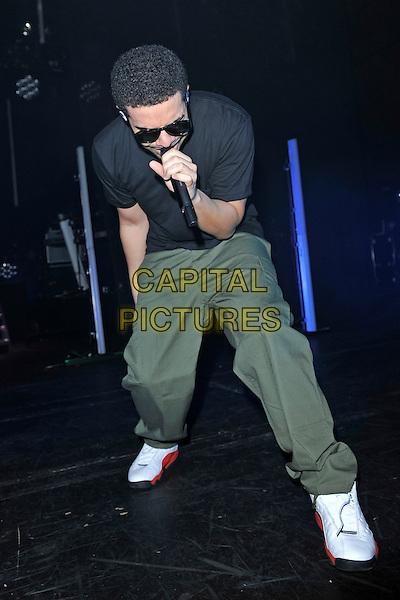 DRAKE (Aubrey Drake Graham).Performing live at Hammersmith Apollo, London, England..January 10th, 2011.stage concert gig performance music full length black t-shirt green combat trousers sunglasses shades singing sneakers trainers .CAP/MAR.© Martin Harris/Capital Pictures.