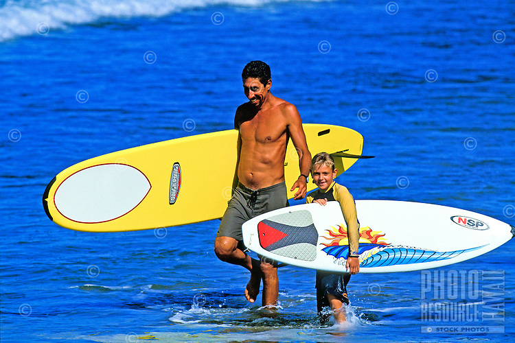 A fit dark haired man carrying a bright yellow surfboard wades in the blue water with a smiling young boy carrying a white surfboard at his side.