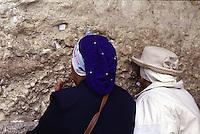 ISRAELE, Gerusalemme. Due turiste pregano al Muro del Pianto di Gerusalemme. Si intravedono i fogliettini con le preghiere inseriti nel muro.