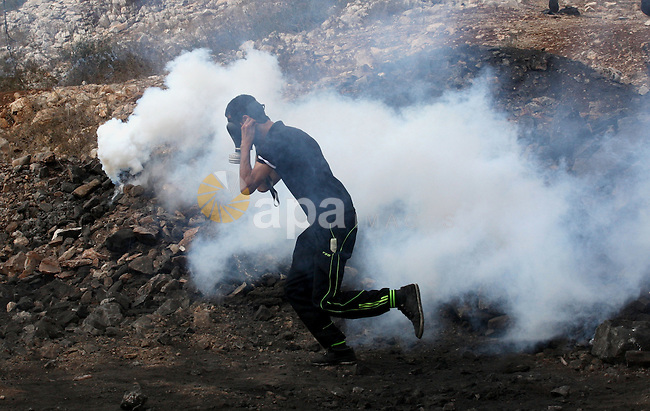 A Palestinian protester wearing a mask throws stones towards Israeli security forces during clashes following a protest on September 5, 2014 in the village of Kfar Qaddum, near the northern city of Nablus, in the occupied West Bank. Israel said it published tenders for 283 new homes in a West Bank settlement, just days after announcing its biggest land grab on occupied Palestinian territory for three decade. Photo by Nedal Eshtayah