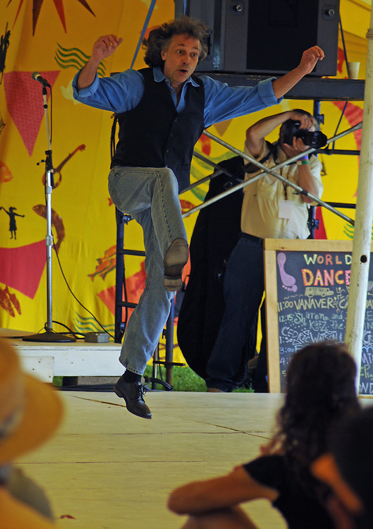 """Matt Gordon, of the Vanaver Caravan Dance troupe, dancing during the group's performance of,  """"Pastures of Plenty: Tribute to Woody Guthrie"""" on the Dance Stage of the 2012 Clearwater Festival at Croton Point Park on Sunday, June 17, 2012. Photograph taken by Jim Peppler. Copyright Jim Peppler/2012."""