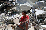 A Palestinian boy sets on the rubbles of his house after demolish by Israeli municipality bulldozers under the pretext of building without permit, at Jabal al-Mukaber district, East Jerusalem May 14, 2014. Israel destroyed more than 500 Palestinian properties in the West Bank and East Jerusalem in 2013, displacing over 850 people, according to UN figures. Photo by Saeed Qaq