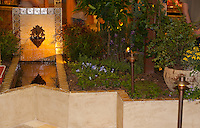 "A fountain pours water inot a tile-lined pool surrounded by plants and plaster walls.  The Orange Coast College Hotriculture Club entered the 2011 Spring Garden Show landscape design competition (http://www.springgardenshow.com/) and won first place in the student category for their ""Moorish Flourishes in a Contemporary Garden"" design."