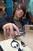 Teenage boy playing finger skateboarding on a model ramp; North East England,
