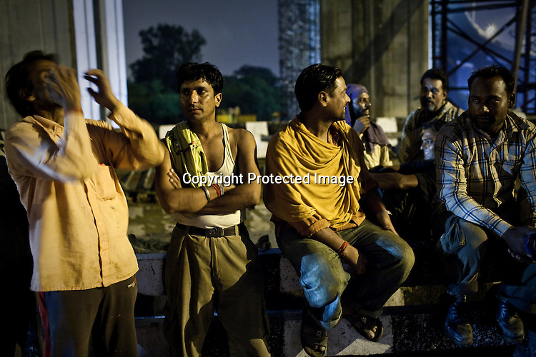 Indian labourers take a break from work (during rain) under the Barapullah Nallah bridge that connects the main stadium to the commonwealth village for the approaching 19th Commonwealth Games 2010 in New Delhi, India.