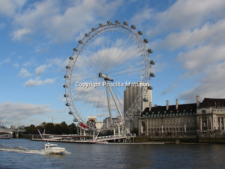 London, England - October 31, 2006:  A boat motors along the Thames in front of County Hall and the London Eye ferris wheel.