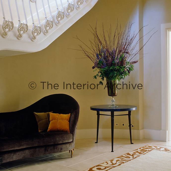 A large flower arrangement stands next to a velvet upholstered chaise-longue beneath a grand staircase in this entrance hall