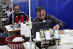 Palestinians work at a clothing factory, at the Karni industrial zone, before exporting to Israel, in the east of Gaza city on March 06, 2019. Head of UniPal 2000, Bashir Al-Bawwab, said that in the 2015 was the first time he has been able to export clothes to Israel since 2007. Photo by Mahmoud Ajjour