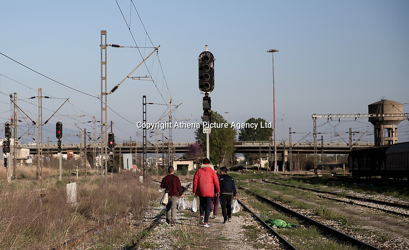 Pictured: Migrant men walk on the track of the OSE freight depot in Thessaloniki, Greece. Wednesday 05 April 2017<br /> Re: A year after an agreement was signed between Greece and Turkey for the management of refugees. Migrants, mostly from Morocco, Algeria and Tunisia, have been living in disused train carriages at the Thessaloniki freight depot of OSE in northern Greece, the company managing the railways in the country. Some of the migrants climb onto moving trains, or even hide themselves in storage areas, hoping that they will cross the border.