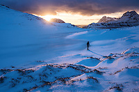 Female hiker with snowshoes at winter dawn on way to Ryten, Moskenesøy, Lofoten Islands, Norway