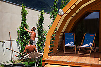 Switzerland. Canton Ticino. Tenero. Camping Campofelice. Tourists have the opportunity to rent private bungalows, called Igloo Tube Home. The innovative bungalows are made of wood and have electricity from solar energy. On the terrace, two blue folding chairs bragging in german language about Ticino charms and the opportunity to extend summer holidays. Two gardeners plant trees for decoration and to hide the wall. 19.07.2018 © 2018 Didier Ruef