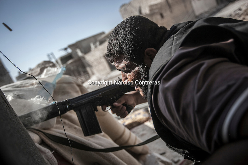 A rebel fighter belonging to the Kateba Omar Ben Abdul Aziz fires to the enemy's position as he repels the army shooting at the Aamria battlefield embedded inside a civilian neighborhood at the southwest of Aleppo City.