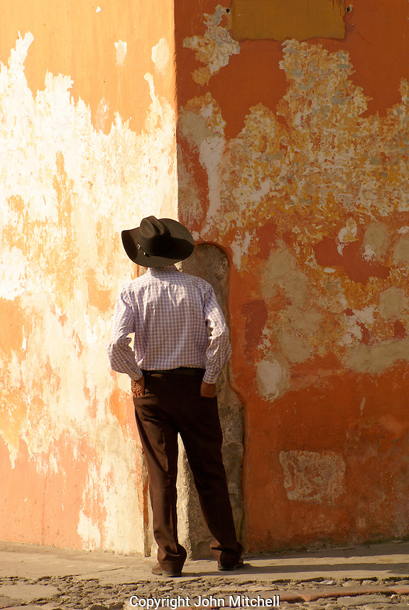 Man standing in front of a colorful wall in Antigua, Guatemala. Antigua is a UNESCO World heritage site...