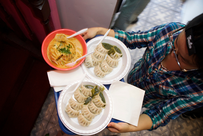Queens, NY - July 10, 2017:  Plates of momos going to diners' tables at Hamro Bhims, a Nepali restaurant in Jackson Heights. A family business, Gyan K Thapa and her children take orders, prep and plate food and serve diners.<br /> <br /> Credit: Clay Williams for Edible Queens.