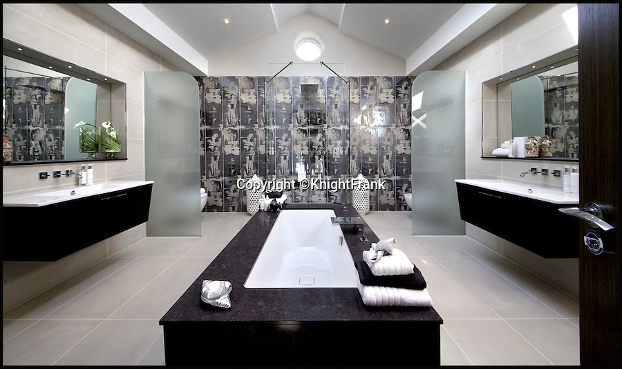 BNPS.co.uk (01202 558833)<br /> Pic: KnightFrank/BNPS<br /> <br /> Bolthole-in-one!<br /> <br /> En-suite bathroom.<br /> <br /> Golf fans will be green with envy - This brand new Palladian style pad comes with a fantastic view of the 17th green at exclusive Wentworth golf club in Surrey.<br /> <br /> But despite the £6.75 million price tag you will still have to pass muster with the members and stump up a £125,000 joining fee to become part of the world famous club.<br /> <br /> Greenside is part of the Wentworth Estate, one of the most expensive private estates in the country, which has the Wentworth Golf Club at its heart.<br /> <br /> The lucky buyer of this house can watch the world's best golfers battle it out for the European Tour's PGA Championship from the balcony overlooking the 17th green of the iconic West Course.<br /> <br /> The newly-built five-bedroom home, on the market with Knight Frank, has everything you could need, including an indoor swimming pool complex with a sauna and a spa.