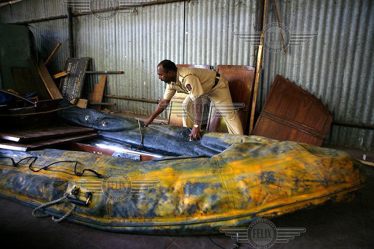 A policeman checks the inflatable rubber raft believed to have been used by the terrorists to enter the city the day multiple attacks were launched in Mumbai on 26/11/2008..