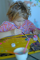 Little blond girl painting in the kitchen, France.