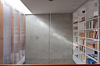 The wall of open shelving contrasts nicely with the thin, transluscent corrugated plastic of the bedroom wall opposite