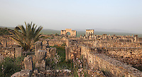General view of Volubilis on a fertile plain in Northern Morocco, seen from the House of Nereids, with the Triumphal Arch of Caracalla, 217 AD, and the Portico, leading to shops on the main street or Decumanus Maximus in the distance. Volubilis was founded in the 3rd century BC by the Phoenicians and was a Roman settlement from the 1st century AD. Volubilis was a thriving Roman olive growing town until 280 AD and was settled until the 11th century. The buildings were largely destroyed by an earthquake in the 18th century and have since been excavated and partly restored. Volubilis was listed as a UNESCO World Heritage Site in 1997. Picture by Manuel Cohen